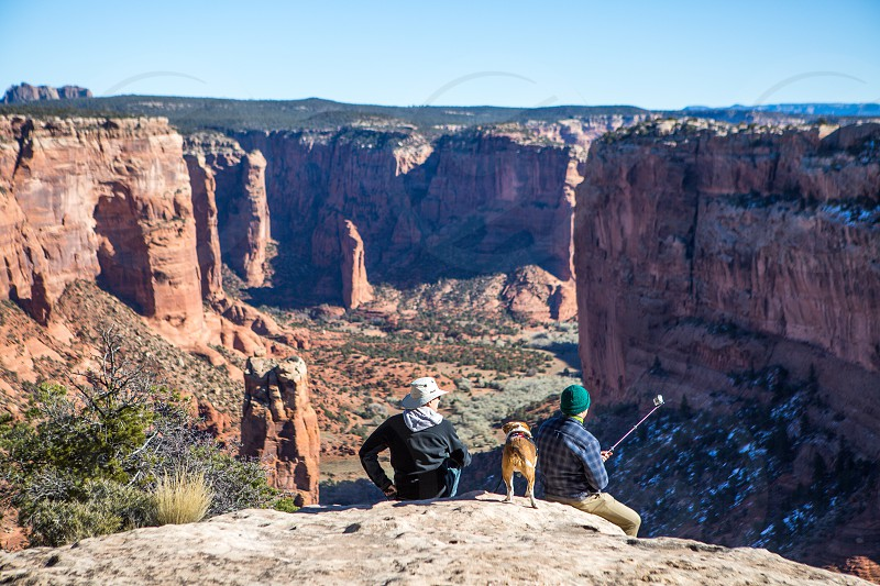 Thanksgiving vacation man and his son with their rescue dog taking a cell phone picture over canyon de chelly national park Arizona photo