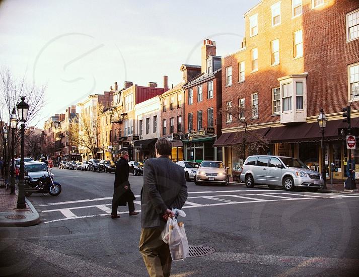 man wearing gray suit walking across road photo