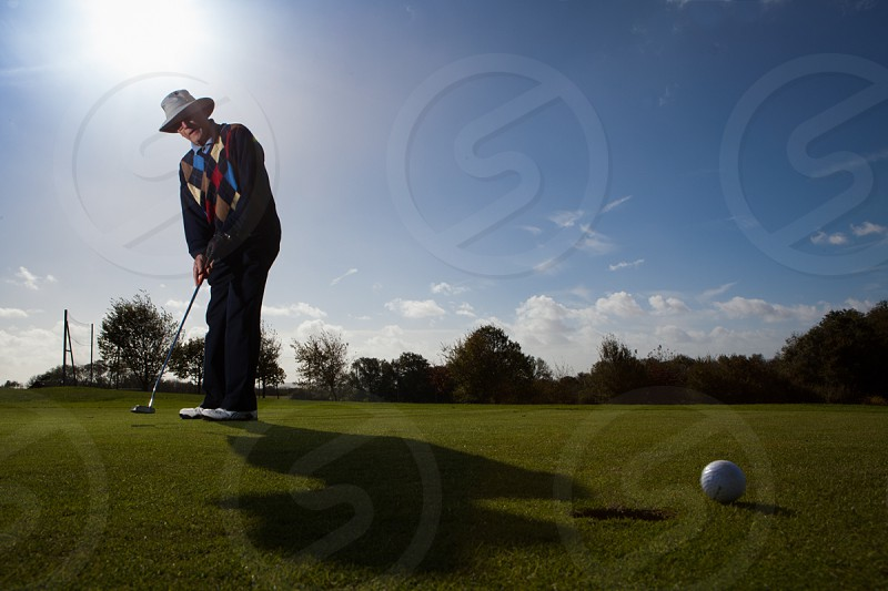 Mature man on putting green with sun behind. photo
