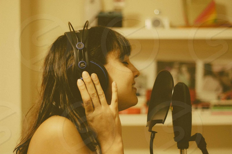brown haired girl singing into microphone wearing headphones  photo
