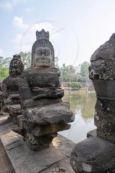 Angkor Wat Temple Cambodia - March 2018: One of the Stone Asuras holding the nāga Vasuki on a bridge leading into the 12th century city of Angkor Thom.  photo
