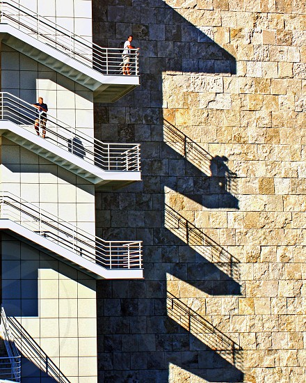 Different levels of exterior stairs with two people on them throw shadows on the building wall. photo