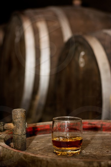 Glass of whiskey on wooden barrel with other barrels in the background in distillery warmer tones. photo