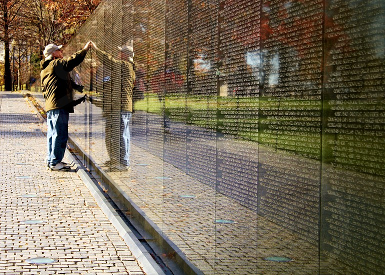 Man touches the Vietnam Veteran's Wall memorial when he find's a friend's name. photo