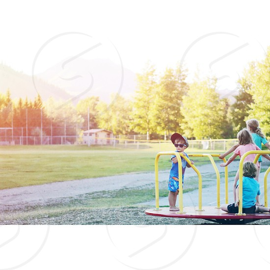 children on yellow spinning playground toy photo