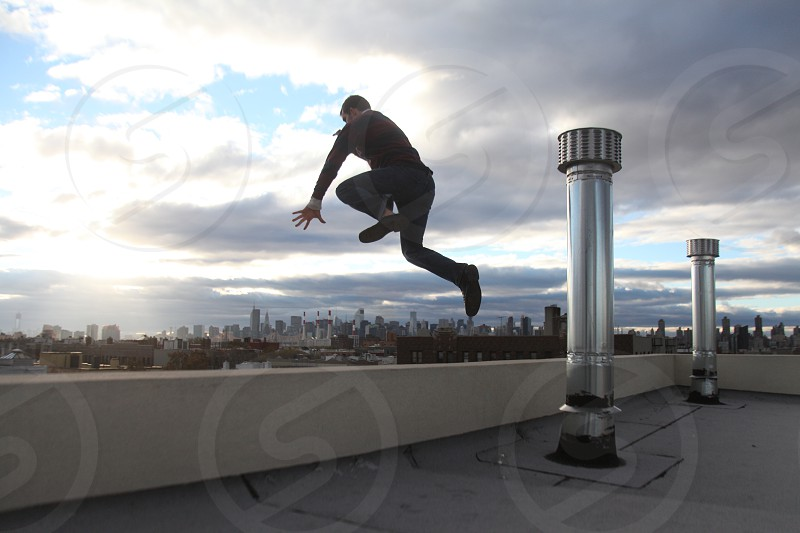 man jumping building ledge new york city new york roof rooftop photo