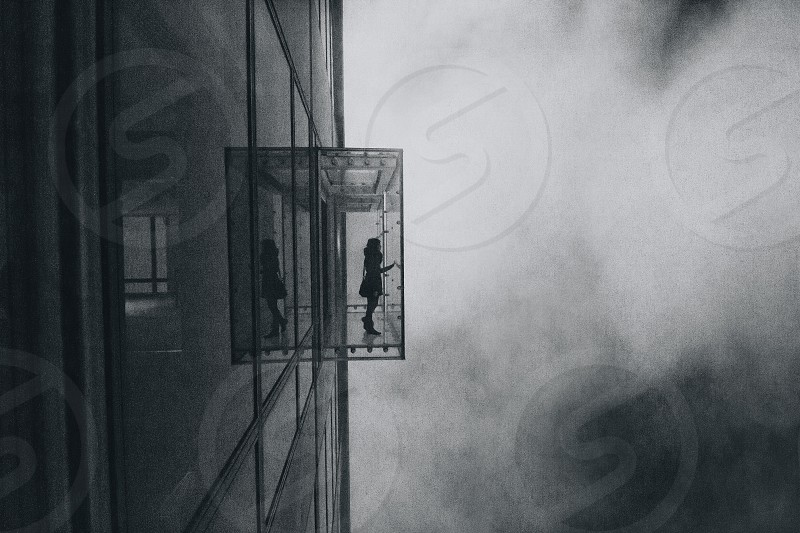 woman in clear glass building grayscale photo photo