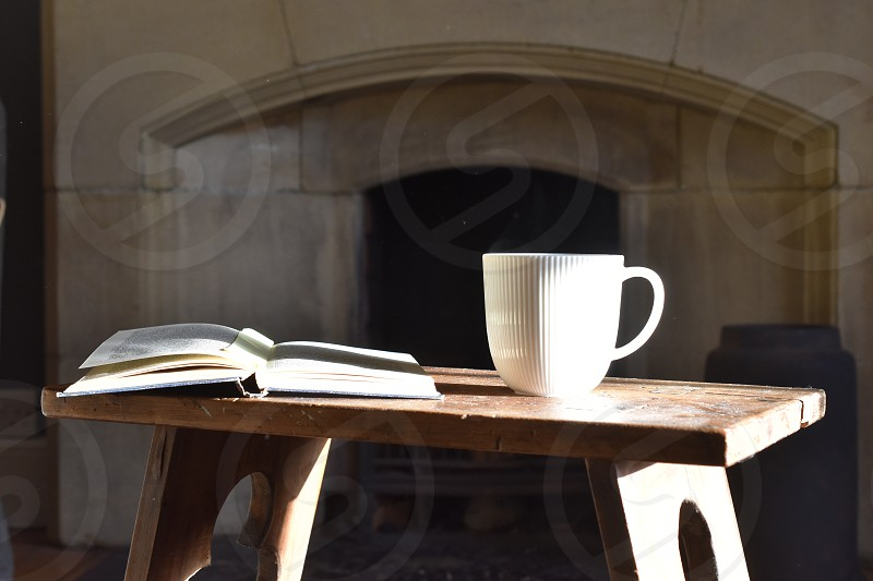 Tea mug and book on a stool in front of a stone fireplace. photo