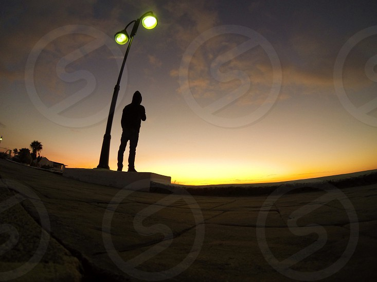 man standing under street light photo