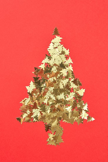New Year creative decorative tree handmade frome shiny small spruces on a red background with place for text. Greeting holiday card. photo