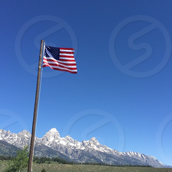 United States flag; stars and stripes; mountains; majesty; snow caps; America; Grand Tetons; Wyoming photo