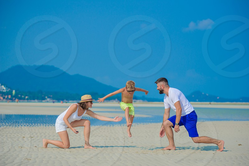 Young family of three: mom dad and a handsome eight years son having fun on the sunny sandy beach they are jumping and flying. photo