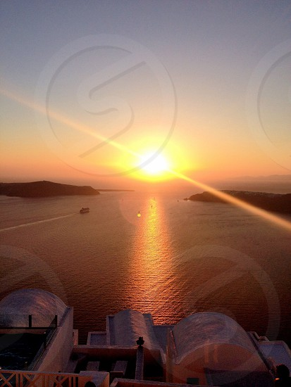 The famous Santorini sunset the boats go out to take a closer look the cruise ship leaving at sunset photo