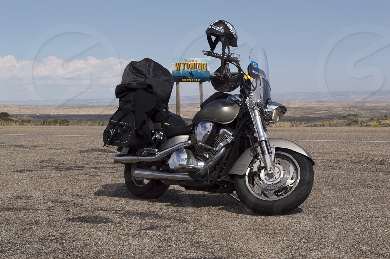 Motorcycle with luggage with the barren landscape of the Wyoming - Utah border and the Welcone to Wyoming sign in the background photo