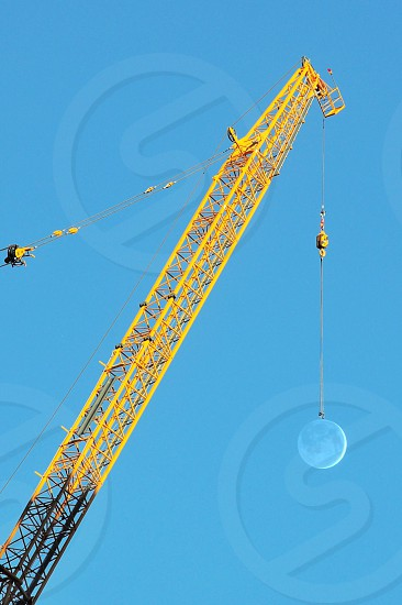 crane tower hooking the moon in forced perspective photograph photo