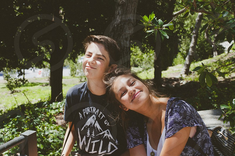 woman head leaning on boy shoulder while smiling photo