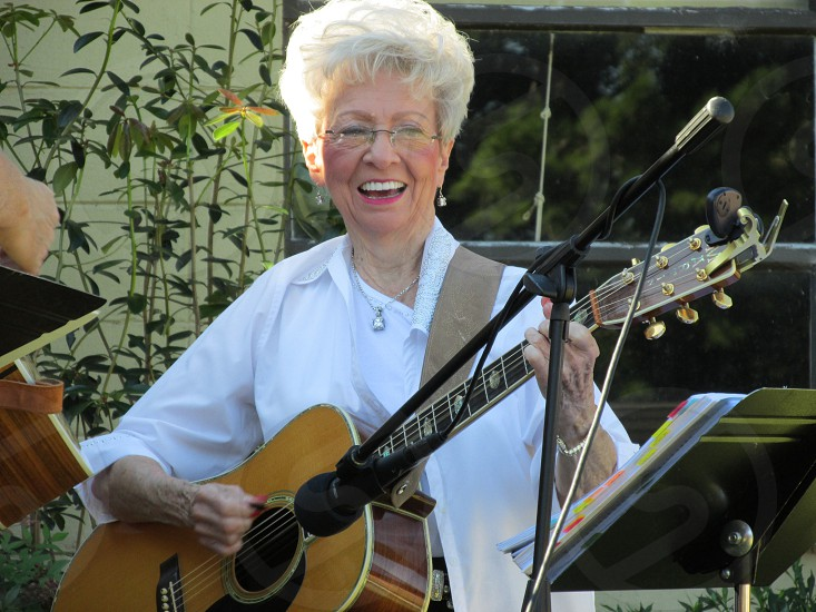 woman with short gray hair smiling and playing acoustic guitar in white shirt on stage photo