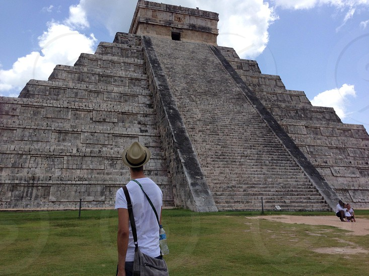 man wearing white shirt near pyramid photo