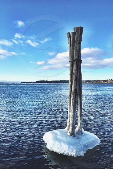 three standing gray poles on white ice floe on large body of water photo