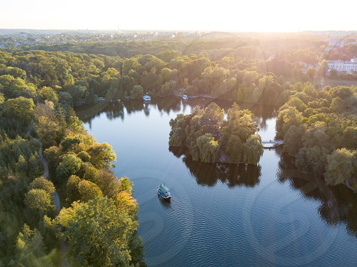 Aerial view from drone of countryside landscape with amazing natural greenery blue river with ships on sunset summer background. Sofiyivsky park city Uman Ukraine photo
