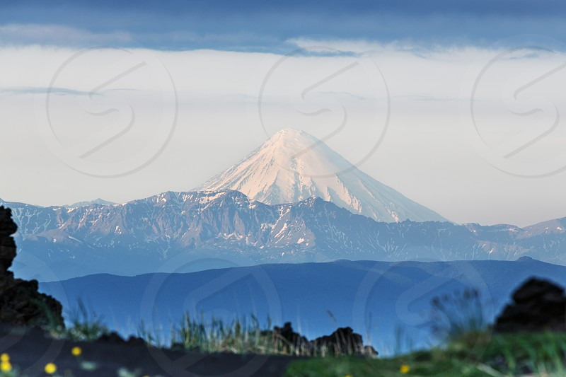 Beautiful summer volcanic landscape of Kamchatka Peninsula: view of active Kronotskaya Sopka (Kronotsky Volcano) in good weather at sunrise. Eurasia Russian Far East Kamchatka Region. photo
