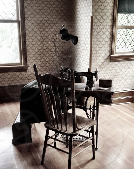black sewing machine beside brown wooden chair photo