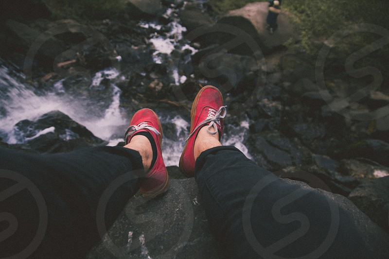person in black pants and red plimsoll shoes photo