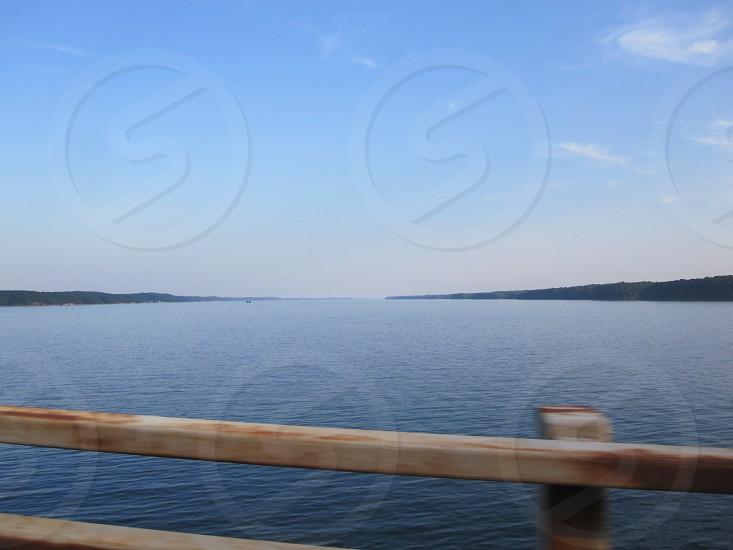river body of water horizon bridge blue sky clouds photo