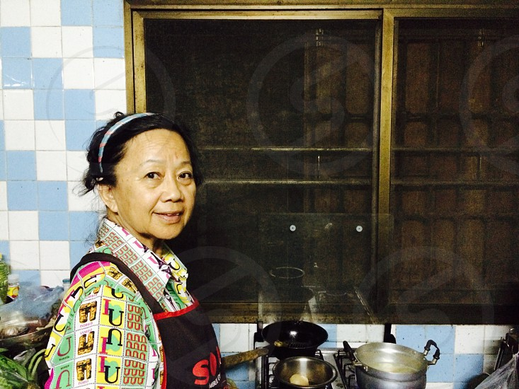 Close up portrait of senior Asian woman cooking in kitchen photo