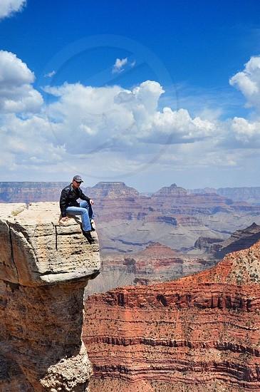 man at rock top looking down photo