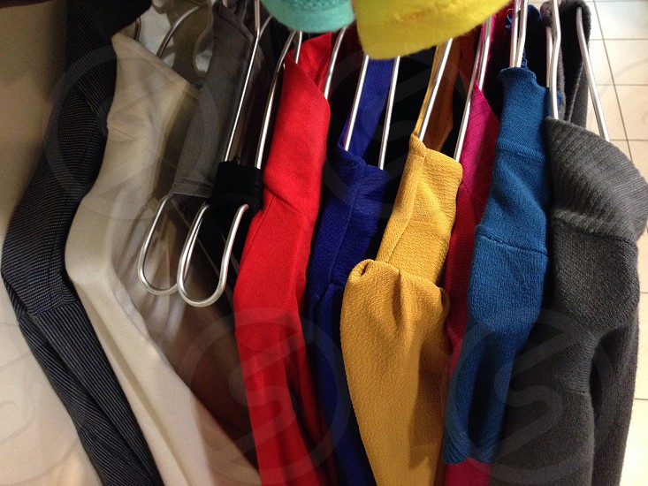 various sweaters on white hangers photo