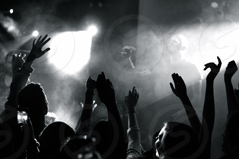 people raising their hands while watching band performing on concert stage greyscale photography photo