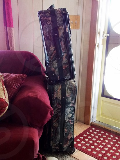 black gray yellow and red floral patterned luggage next to red fabric sofa photo