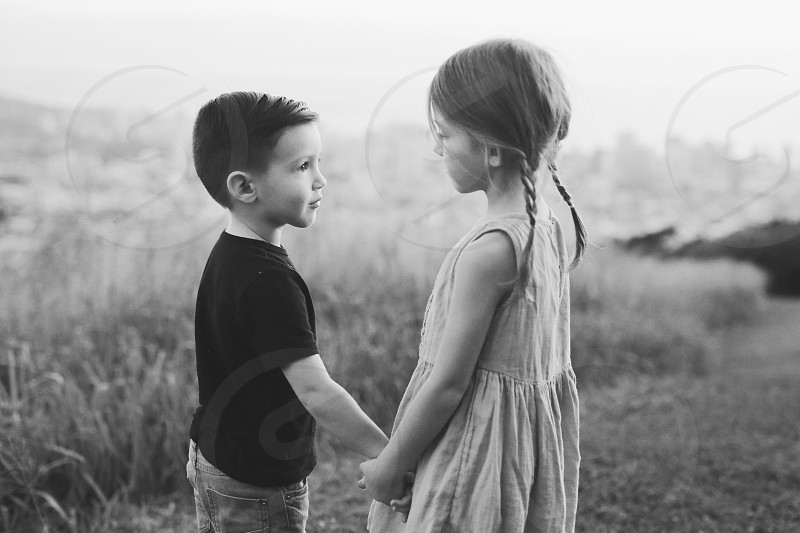 grayscale photo of boy wearing t shirt and girl wearing sleeveless dress holding hands photo