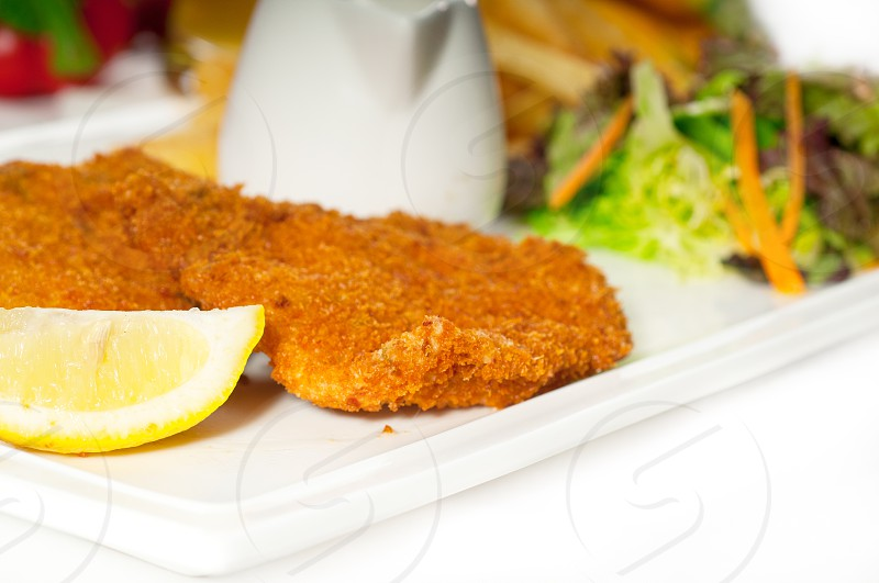 classic breaded Milanese veal cutlets with french fries and vegetables on background MORE DELICIOUS FOOD ON PORTFOLIO photo