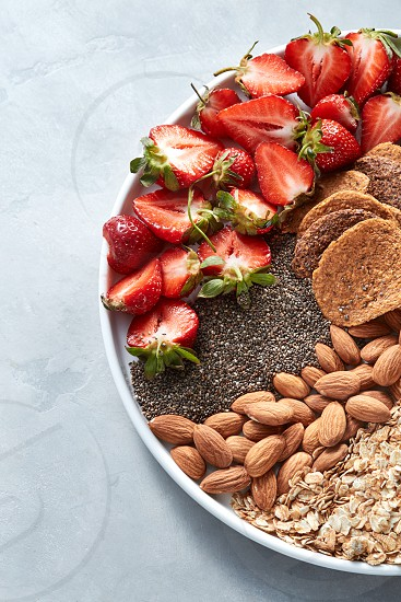 Organic fresh ingredients for healthy homemade natural breakfast - berries granola nuts chia seeds on a gray stone table for place for text. Healthy vegan background. Flat lay photo
