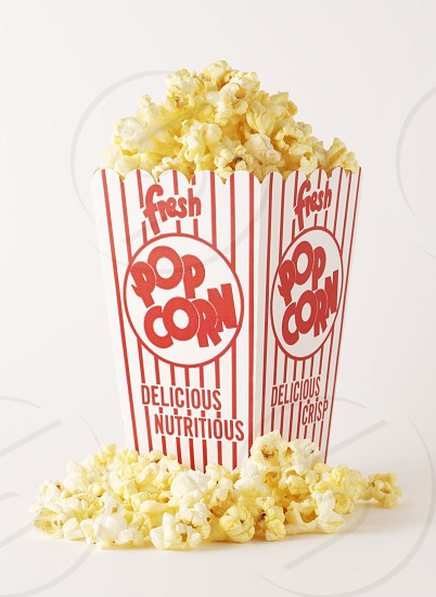 FOOD POPCORN WHITE BACKGROUND ISOLATED ON WHITE RED LETTERS POPCORN BOX SEAMLESS MOVIE THEATRE POPCORN VERTICAL STUDIO SHOT INDOORSYELLOW HEALTHY LIFESTYLE photo