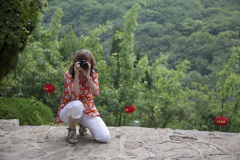 woman in white capri pants using black dslr camera photo