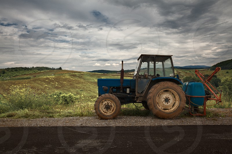 Village lifestyle old used tractor parked besides the road summer season.  photo