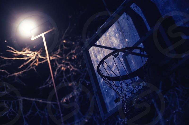 Basketball hoop in dark illuminated by basketball yard lights.  photo