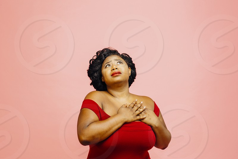 Woman holding her chest and looking up scared and uncertain isolated on pink  photo