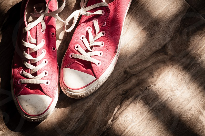 Classic converse sneakers in pink on wood with interesting light. photo