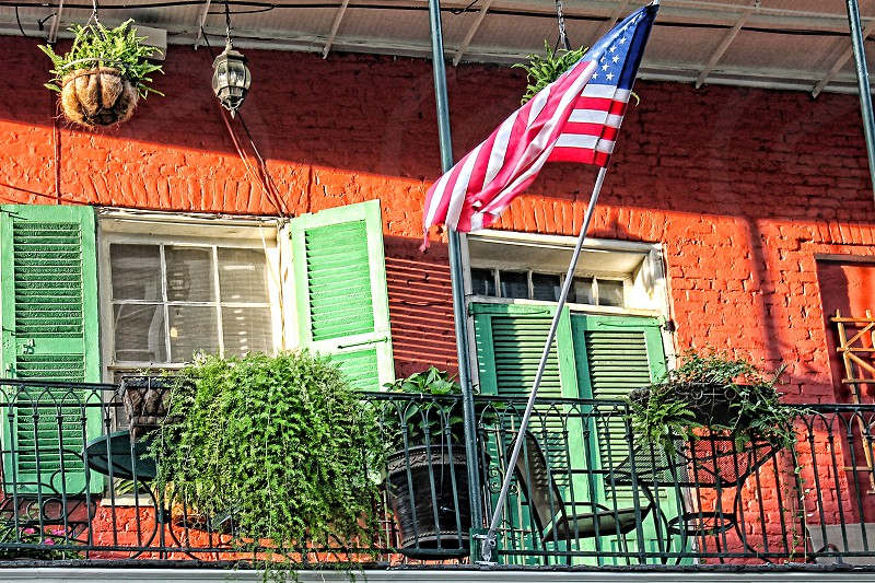 Fourth of July celebration in the French Quarter of New Orleans NOLA with an American flag handing outside a colorful patio  photo