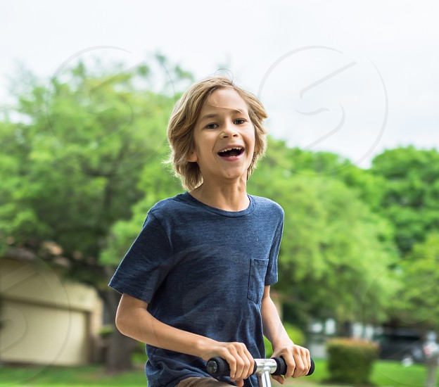Boy young playing fun youth smiling laughing ridding scooter  photo