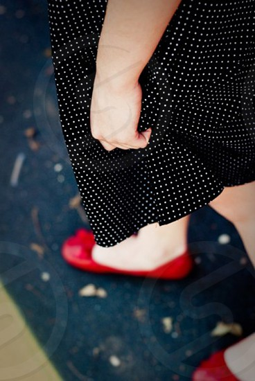 woman in white polka dot black skirt and red flats photo