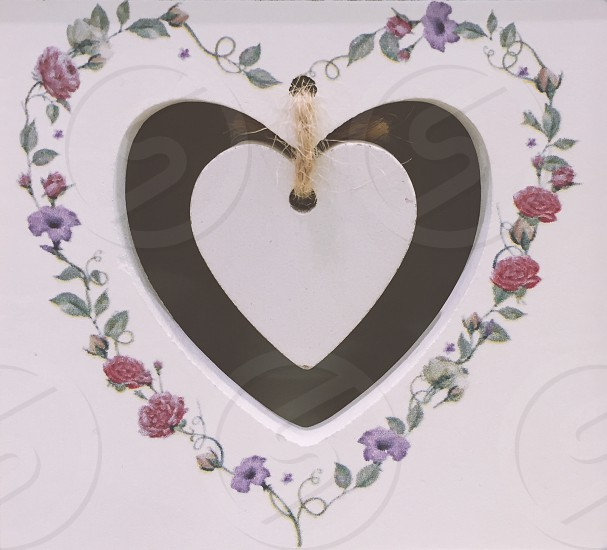 white wooden cutout heart board with purple and red floral heart-form painted border photo