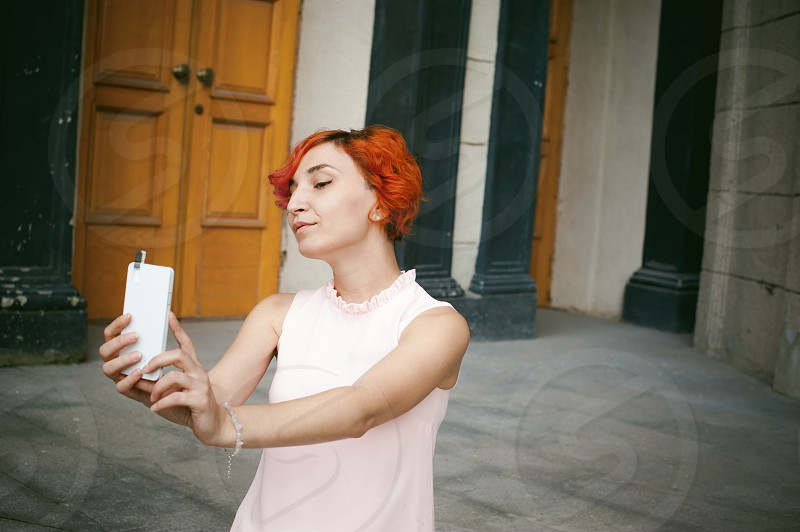 portrait of a girl doing selfie. girl in light pink dress with red dyed hair pictures of themselves on their mobile camera phone sitting on the stairs summer day photo