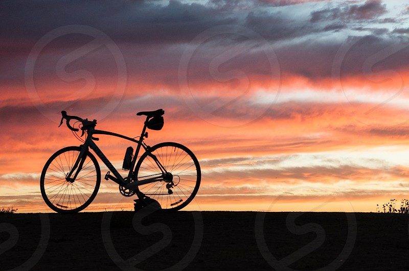 Road bike with gear silhouetted against a sunset sky. photo