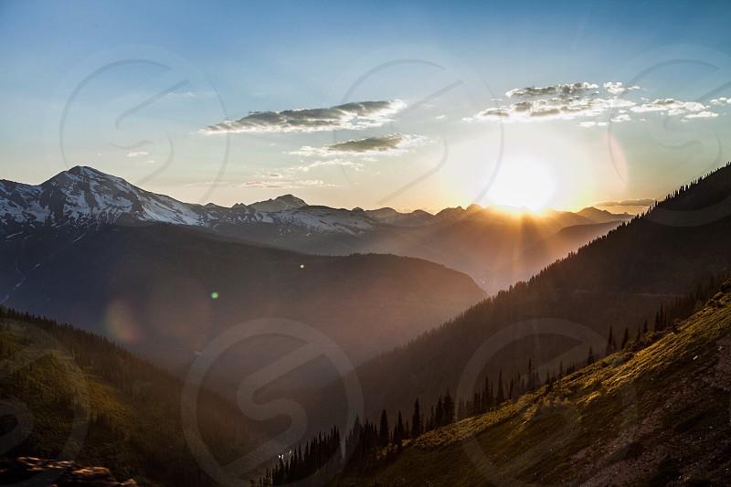 Each sunset promises another sunrise. Sunset mountains fog light trees landscape photo