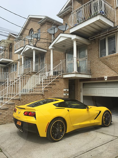 yellow and black corvette parked near brown building photo